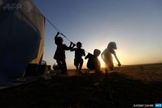 IRAQ, ASKI KALAK : Iraqi children play on the guideline of a tent set-up in a temporary camp, set up to house civilians fleeing violence, in Iraq's northern Nineveh province, in Aski kalak, 40 kms west of the Kurdish autonomous region's capital Arbil, on June 14, 2014. Shiite Iran offered to consider working with longtime foe the United States if it takes the lead in helping push back Sunni Arab militants, who have seized a swathe of northern Iraq. AFP PHOTO/KARIM SAHIB