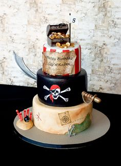 Pirate Birthday Cake This is a 3 tier white cake covered in LMF. All the added elements are made of out gum paste. I used wafer paper for...