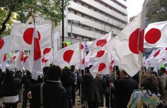 Participants at a rally organized by a conservative group hold up Japanese flags at a park in Osaka. (Akira Kudochi)