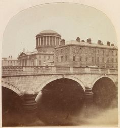 August 1861 photo of the Four Courts building featuring a domed tower above a neo-classical façade of the court building which stands in the background. In the foreground stands the O'Donovan Rossa Bridge spanning the River Liffey. Erroneously titled as 'Trinity College, Dublin', this is a photograph of The Four Courts which comprise the High Court, The Supreme Court, The Court of Appeal and the Dublin Circuit Court. Construction of the building began in 1786 and was not complete until 1802.