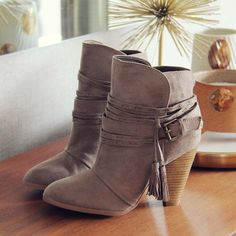 "Gorgeous strappy & tassel details adorn these darling booties. Designed with a stacked heel, soft suede outer, and wrapped buckle strap & tassel details. Darling worn with dresses or skinnies.  Color: Taupe Heel Height: 3 1/2"" Vegan Suede"