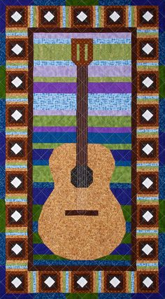 Solo Guitar is a quilt art wall hanging design representing a stylized image of a classical acoustic guitar. The central panel is constructed in rows, forming colorful horizontal stripes in the background behind the guitar. Optional top stitching is used to suggest guitar strings. The border is made from 24 small blocks of concentric squares surrounding a diamond center. The border design is suggestive of the rosette patterns that are often inlaid around a guitar's sound hole.  The wall…