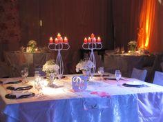 La mesa principal con velas, flores y candelabros.