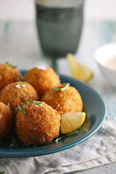 Crab Croquettes made as balls of creamy mashed potatoes stuffed with cajun seasoned crab, sweet corn, smoky bacon, and sharp gruyere cheese that are deep fried to golden perfection and then drizzled or dipped in a creamy cajun lemon sauce with fragrant fresh basil.