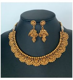 Antique Gold finished necklace set with matching Jhumkas /South Indian Jewelry/ Antique necklace / Temple jewelry #antique #gold #jewelry #indian #mangalsutra #antiquegoldjewelryindianmangalsutra An elegant antique gold set for your local gatherings or parties. Height of the earrings: 5.3 cm Width of the earrings: 2 cm Care Instruction : Avoid Heat & Chemicals Like Perfume, Deo, Alchol, Etc. | Clean With Dry Cotton Cloth | Pack In our Anti tarnish box after use. Gold Jewellery Design, Gold Jewelry, Bridal Jewelry, Jewelry Sets, Antique Necklace, Indian Jewelry, South Indian Bridal Jewellery, Necklace Designs, Necklace Set