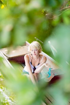 Woman relaxing on the vintage wooden boat. - Thoughtful young blonde woman enjoying the sunny summer day on a vintage wooden boats on a lake in pure natural environment on the countryside.