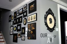tracy's wall of art. love the thick black frames, sillohuette with yellow and curly black frame, and crowded arrangement