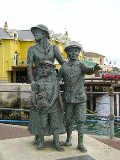 "On the Cobh waterfront. ""Annie Moore and her brothers Anthony and Philip embarked from this town on 20 December 1891 on the S.S. Nevada. Annie was the first person to be admitted to the United States of America through the new immigration centre at Ellis Island, New York on 1 January, 1892. It was Erected by Cóbh Heritage Trust Ltd. and is dedicated to all who emigrated from Ireland."" ""This sculpture is the work of Jeanne Rynhart of Bantry."""