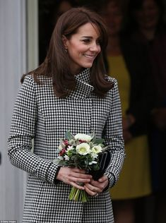 Kate smiles after being presented with a bouquet of cream and red flowers ...