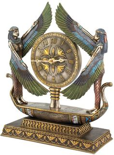 "Wings of Isis Egyptian Revival Sculptural Clock- With wings spread to showcase a beautiful quartz clock with hieroglyphic numerals, double Isis figures ride a foot-long barge to the Afterworld in this stunning Egyptian Revival work. True to the decorative arts of the 1920's, this quality designer resin statement work blends style and function as it glows in the rich palette of the ancient world. Accepts your single AA battery.  13½""Wx5""Dx16""H. 7 lbs."