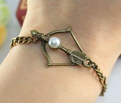 The Hunger Games Inspired Katniss's bow with Peeta's pearl by BeautyandLuck on Etsy.