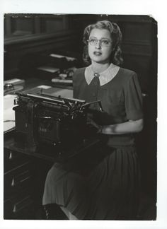 """Double weight, original, vintage photo of the beautiful Jeanette MacDonald even with eyeglasses! Back of the photo states: """"WHAT'S THAT COUNT PALAFFI?.....Jeanette MacDonald asks this as she looks up while typing during one of the amusing scenes in Metro-Goldwyn-Mayer's screen version of the hit Broadway musical, """"I Married An Angel"""", starring Miss MacDonald and Nelson Eddy. - ESCANO COLLECTION"""