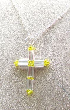 "This delicate beaded cross is beadwoven with high quality Czech silver bugle beads and yellow seed beads.   The Cross is the principal symbol of the Christian faith, symbolizing the death and resurrection of Jesus Christ.  This Cross pendant is approx 1.25"" (3.17cm) in length and just over .75"" (1.9cm) in width. It is lightweight and delicate with just enough weight to keep it hanging comfortably."