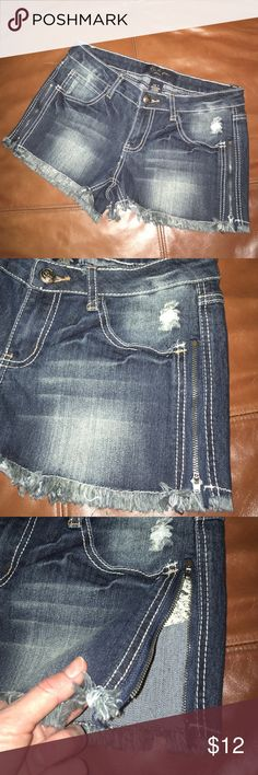 Denim shorts with working side zippers and fringe Shorts have fringe at bottom and factory distressing. Look cute with sides unzipped with a swimsuit.  Earl Jean brand. Excellent condition. Don't forget to bundle and save🙂 Earl Jeans Shorts Jean Shorts