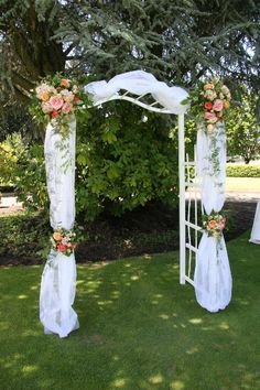 Create a picture perfect backdrop for an outdoor wedding with an arch draped in tulle and accented with a beautiful mix of flowers.  We've created a soft, romantic feel with old-fashioned Tea Roses in pastel colors, Pink Hydrangea, and seeded Eucalyptus.  Flowers by A Floral Affair - www.afloralaffair.com  #wedding #flowers #AFloralAffair