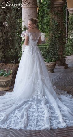 Style 4012: Feel like Cinderella in this sweetheart illusion off the shoulder A-line wedding dress. Corded lace accents the organza skirt. A detachable cathedral train creates the fairy tale with Illusion and lace to end of the train. Buttons finish the illusion back to the covered zipper.