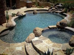 Natural freeform pool and spa with waterfall and decorative boulders. Beautiful desert theme #thunderbirdpools #phoenixpoolbuilder