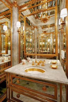 Gilded bronze and mirror-paneled walls create a Faberge-like environment in this jewel of a powder room.
