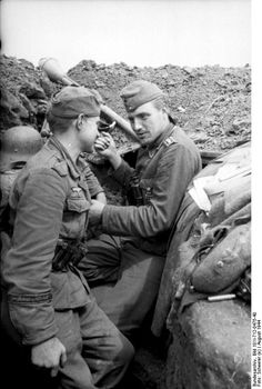 "Two members of the ""Großdeutschland"" Division sit in a trench on the Lithuanian-Latvian border, Dobele, Latvia, August 1944. Laying on the edge of the trench is a Panzerfaust 30."