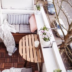 tiny balcony with parquet flooring, folding table, and benches with cushions