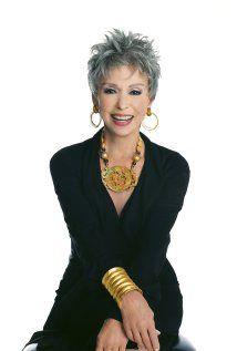 ella lleva una vestido negro, unas pendiente oro, un   collar oro y una pulsera oro.