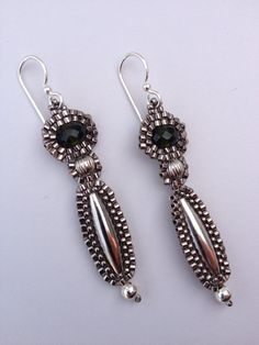 These beautiful earrings have hand stitched beadwork surrounding a long oval silver bead, a fluted nickle silver bead and an oval faceted bottle