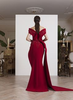 AZZI & OSTA: Off-shoulder fishtail red crepe gown, with sculptural volume on the hips that extend as a train to the side, embellished with red floral sequins