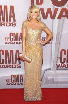 Carrie Underwood wears a glittering golden Reem Acra gown to the 45th CMAs.