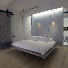 For the swingers!!! Floating bed by Bernstein Architects. Sheet metal sliding door, gray accent wall and hardwood flooring.