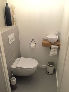 Toilet van Floor en Gyan. Gietvloer - gestucte muren - houten plankje met mat witte kom - ultra dunne toiletbril - zwart stalen toiletrol houder - ikea retro prullenbakje.