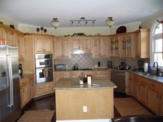 Natural red oak kitchen floors were sanded and stained with a mix of Dark Walnut, Jacobean, Ebony and Mahogany to get this rich darker color; light maple cabinets BEFORE they were painted and glazed