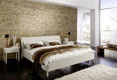 La piedra que decora la pared del cabecero junto con el material en que está realizado el dormitorio crean un atractivo juego de materiales cálidos y fríos.