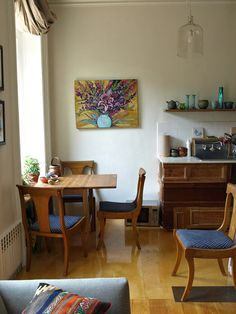 Home of Juliet Gorman & Elliott Malkin. What I love about this photo: the chairs, the painting on the wall, the countertop and wood cupboards.