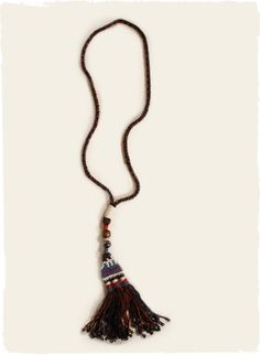 The artisan-made crochet necklace culminates in beaded tassels.