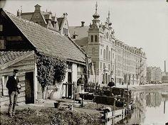 Kerkpad Thans Hugo de Grootkade. Boerderijtje aan de Vinkenbuurtsloot. Gezien naar Hugode Grootkade 2-2A t/m 20A-20B (v.r.n.l.). In het midden de Gereformeerde Raamkerk. Uiterst rechts is Marnixstraat 305 / Bloemgracht 27