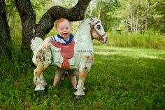 one year old playing on daddy's childhood toy horse