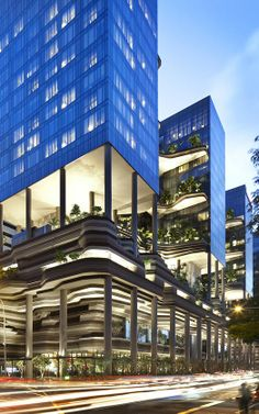 "Designed by WOHA, the block-long ""hotel and office in a garden"" sits on a narrow plot that opens onto Singapore's central business core and is situated across from a verdant parkland and near the riverbank. Slab-like towers, which echo those rising in downtown just in the distance, are suspended above a green zone of tangled flora and palm trees that thrive in the tropical climate. The vegetation is rooted to curved terraces that are themselves fixed to the towers' glass facades."