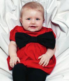 The Tiny Universe Jurk The Tiny Red Rood  Te schattig voor woorden! Een feestelijke rode ballonjurk wijd uitlopend met een enorm grote strik aan de voorkant en brede bies rondom de middel. Ronde hals met links van de hals voorzien van druksluiting. Korte mouwen voorzien van pofmouwen. Achterkant van de hals is voorzien van een opgestikte label: THE TINY UNIVERSE  Kleur: Rood/Zwart Materiaal: 100% Katoen Verkrijgbaar in maat: 80