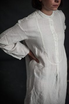 Introducing THE LABEL. Ready to wear in soft laundered linen. Oversized grandad shirt dress in indigo or white enzyme washed linen, with a curved shirt front hem line, 5 buttons, small side splits and a straight back hem. Loose fitting and easy to wear on its own or over trousers. Woven and made in Lithuania. DRESS LENGTH UK SIZING