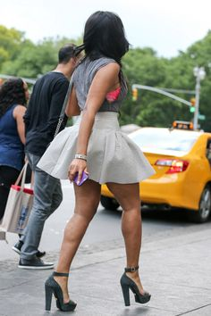 Angela Simmons showed off her stems in NYC in a $18 H&M Linen Blend Tank Top, pleated mini skirt, and $895 Prada Ankle Strap Platform Sandals