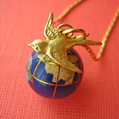 """Wherever you are in the world, you'll always be close to the one's you love!This delightful little gemstone globe bead has hand inlaid continents crafted from dyed Mother Of Pearl. Sweeping around the world is a little brass swallow charm, making his way home.Hung from a 24"""" gold plated vintage chain. The blue glass globe is 15mm or 5/8"""" across. FEATURED BY Cosmopolitan magazine. As worn by Eliza Doolittle, Peaches Geldof and Pixie Lott."""