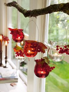 Candles hanging within tinted jars from a branch. Beautiful fall decor.