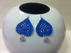orecchini all'uncinetto,dipinti a mano nei toni del blu cobalto.vetrificati,con glitter in tinta.A forma di cuore con pendente trasparente