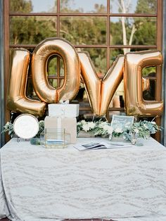 Metallic Gold LOVE Balloons for a Wedding Welcome Table