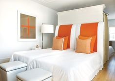 White guest bedroom in a Florida beach house with a large orange stripe on the headboard and orange accent pillows