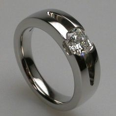 High polish cushion cut diamond flush set in 14k white gold. Because these rings are custom made, any metal and stone can be used.