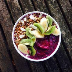 Blueberry smoothie bowl, topped with rawnola, banana & kiwi fruit.