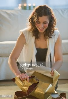 Foto de stock : Woman unwrapping Christmas gift in living room