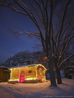 Log cabin decorated with Christmas lights in snow at night