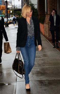 Sienna Miller wears high-waist jeans, a printed blouse and a black blazer.
